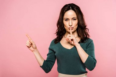 attractive woman showing hush sign and pointing with finger isolated on pink