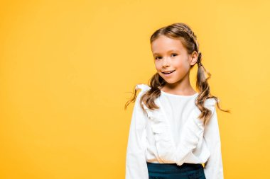 happy and cute schoolchild standing isolated on orange
