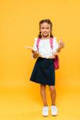 Fotografie šťastný školučitel, který drží knihy a ukazoval palec na oranžovou