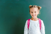 Photo happy kid smiling while standing with backpack on green