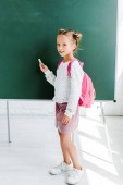 cute schoolgirl standing with backpack and holding chalk near green chalkboard
