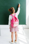 back view of schoolgirl standing with backpack and holding chalk near green chalkboard