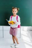 boldog iskolás gazdaság könyv közelében zöld palatboard az osztályban
