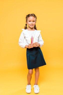 happy schoolkid holding color pencils on orange