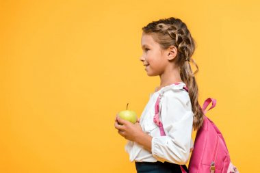 side view of happy schoolkid holding apple isolated on orange