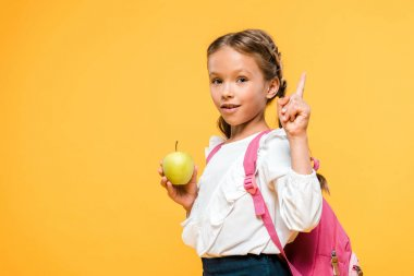 adorable schoolkid holding apple and pointing with finger isolated on orange