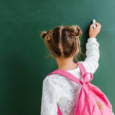 back view of kid holding chalk near chalkboard on green