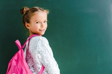 happy schoolkid smiling while standing with backpack on green