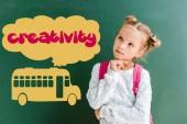 Fotografia bambino pensieroso in piedi con zaino vicino alla lavagna con scuolabus e creatività lettering sul verde