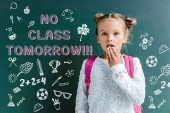 surprised schoolgirl covering mouth near chalkboard with no class tomorrow lettering on green