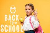 Rozkošný školák s jablkem a ukazováčku v blízkosti od školních letí na oranžovém