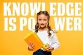 Fotografie šťastné školní dítě s chutným jablkem a knihami blízko vědění je písmo na oranžovém