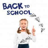 boldog gyerek mutatva ujjal vissza az iskolába betűkkel a fehér