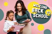 glückliche Mutter steht neben süßer Tochter und begrüßt zurück in der Schule Schriftzug beim Malen auf rosa