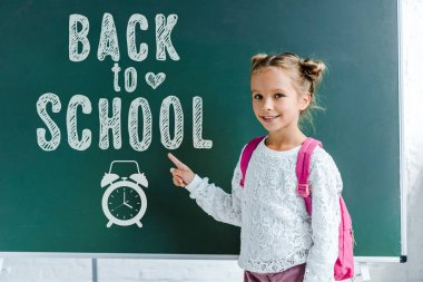 cheerful kid smiling while pointing with finger at back to school lettering on green chalkboard