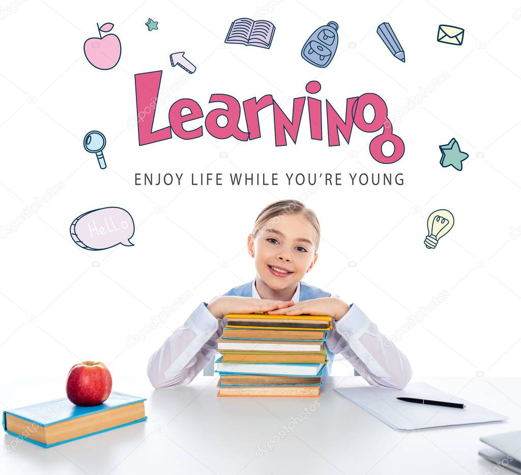 Smiling schoolgirl sitting at desk with books and looking at camera near learning lettering on white stock vector