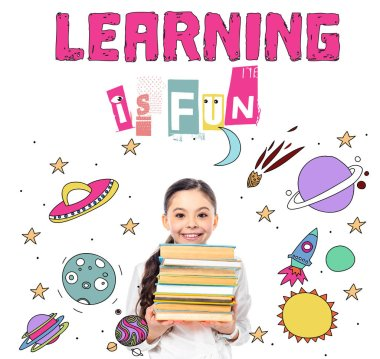 Smiling schoolgirl holding books and looking at camera near learning is fun letters on white stock vector