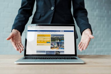 KYIV, UKRAINE - AUGUST 5, 2019: cropped view of woman gesturing near laptop with booking website on screen stock vector