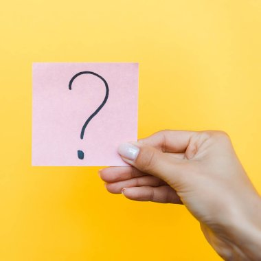 Cropped view of woman holding pink sticky note with question mark isolated on orange stock vector