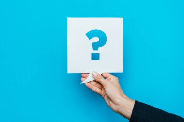 cropped view of woman holding speech bubble with question mark on blue