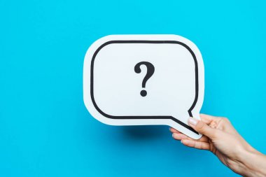 cropped view of woman holding white speech bubble with question mark on blue