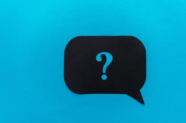 top view of of black question mark on speech bubble isolated on blue