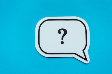 top view of of black question mark on white speech bubble isolated on blue