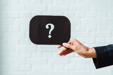 cropped view of woman holding black speech bubble with question mark near white brick wall