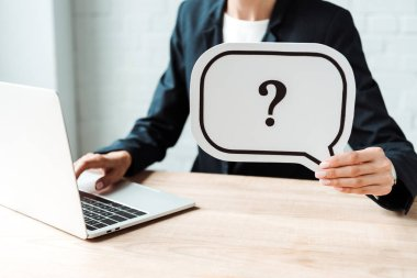 cropped view of woman holding speech bubble with question mark while working in office