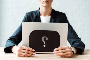 cropped view of woman holding black speech bubble with question mark while sitting in office