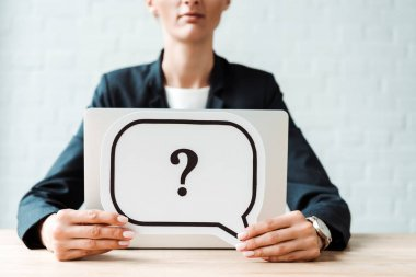Cropped view of woman holding black speech bubble with question mark near desk stock vector