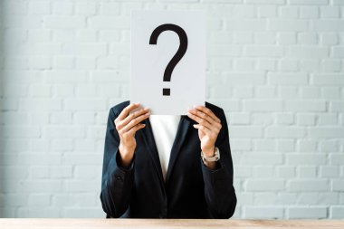 Cropped view of woman covering face while holding placard with question mark near brick wall stock vector