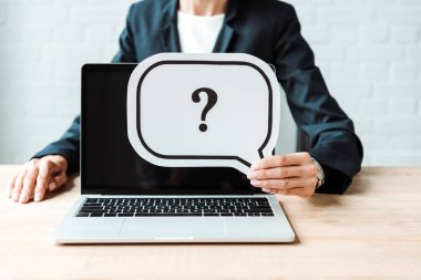 Cropped view of woman holding speech bubble with question mark near laptop stock vector