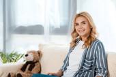 šťastná žena sedí na pohovce poblíž Měkké hračky