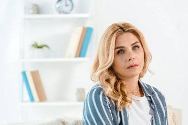 sad woman with bad mood looking at camera in living room