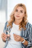 Frau blickt in Kamera, während sie Glas mit Wasser und Tablette in der Hand hält