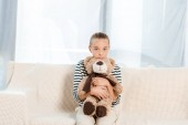 cute kid holding teddy bear while looking at camera and sitting on sofa