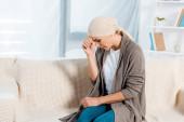 Fotografie verärgerte und kranke Frau mit Kopftuch im Wohnzimmer