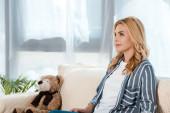 atraktivní žena sedící na pohovce nedaleko medvídka