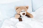 mackó ágyon, fehér ágynemű és párnák