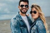 Photo attractive woman and handsome man in denim jackets looking at camera