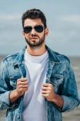 Photo handsome man in denim jacket and sunglasses looking at camera