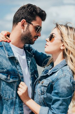 Attractive woman and handsome man in denim jackets hugging and looking at each other stock vector