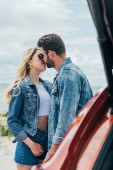 Photo attractive woman and handsome man in denim jackets kissing outside