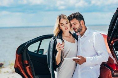 akıllı telefon ve dijital tablet tutan yakışıklı adam kullanarak çekici kadın