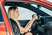 Photo side view of attractive and blonde woman in black jacket driving car