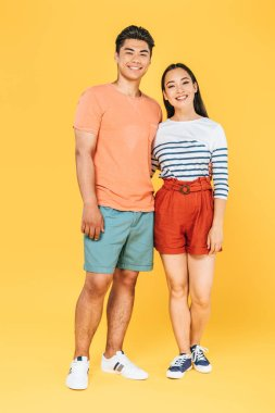 Cheerful asian couple in summer clothing looking at camera on yellow background stock vector