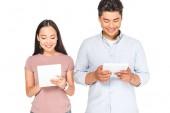 Veselý asijský pár používající digitální tablety izolované na bílém