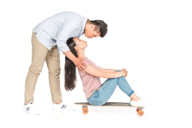 Handsome asian man embracing and kissing girlfriend sitting on longboard on white background stock vector