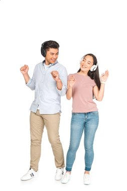 happy asian couple looking at each other while listening music in headphones and dancing on white background